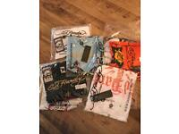 11 T Shirts, various sizes, various styles. All in bags never worn.
