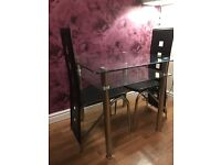 Glass dining table and two black chairs