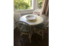 White round dining table with 4 chairs