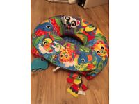 Baby doughnut chair with toys.
