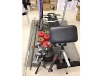 Weights Bench press with various plates, barbells, dumbbells and exercise bands