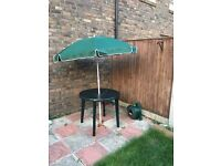 dark green round garden table with umbrella