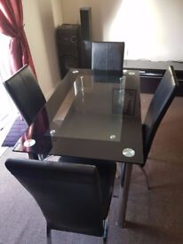Glass Dining table with four black leather chairs all in good condition. Non-Delivery