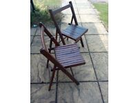 Two vintage dark wooden folding chairs