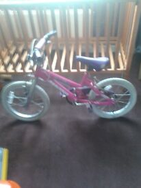 here is a pink childs bike clean and tidy .