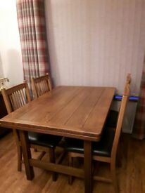 Solid oak dining table and four chairs. Only £200!