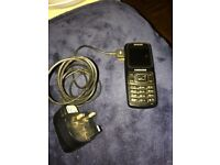 Samsung black SGH-B130 mobile phone with charger