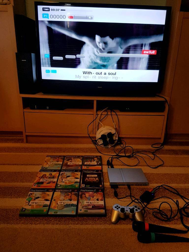 Silver Slimline PS2 console with 9 singstar games with singstar Mics
