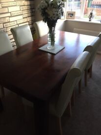 Solid table with 6 faux leather chairs. Two chairs will need recovering