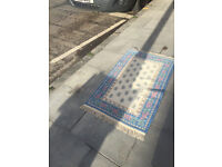 Small cream rug with blue colours . Size 132cm x 74cm. In good condition.