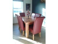 Oak extending dining table and 6 red faux leather chairs