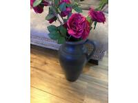 Artificial flowers in grey vase