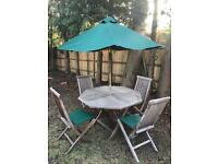 Wooden table and chairs with green umbrella and seat cushions
