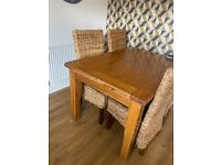 Oak extending dining table and rattan chairs