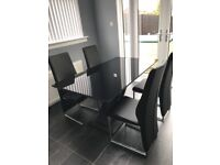 Black glass dining table & 6 chairs nearly new 6months old redecoration is forcing the sale!