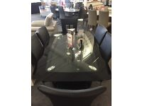 Black and clear glass dining table with chrome legs and 6 leather chairs