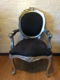 Beautiful and unique armchair. Navy blue leather upholstery with silver wood detailing