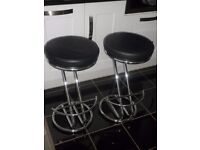 Two chrome bar/kitchen stools with black leather seats.