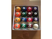 Two sets of pool balls, cues and spider