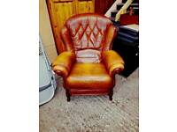 Leather button back armchair with dark wood trim