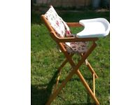 Folding Baby High Chair. Pine wood legs, vinyl seat for easy cleaning.