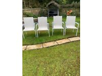 Four white stackable garden chairs