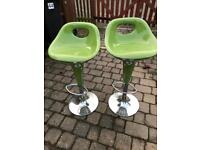 Two green seated aluminium bar stools