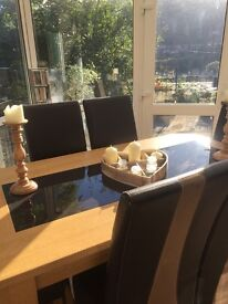 Harvey's wood and glass dining table and 6 high back brown faux leather and suede chairs