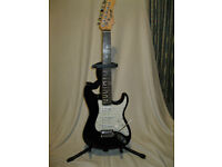 Stagg S300 Stratocaster style black electric guitar with strap.