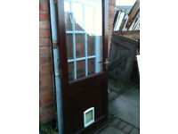 Exterior wooden door with large clear glass panel and cat flap