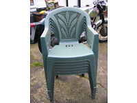 A stack of 6 green garden chairs