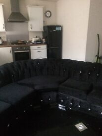 Black crushed velvet rounded section suite & black shiny coffee table