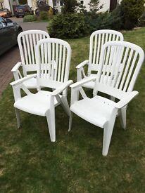 Four reclining plastic garden chairs.