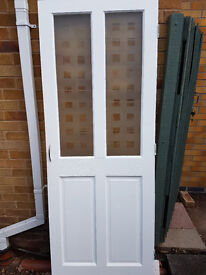 White painted solid wooden door with partial frosted glass panes