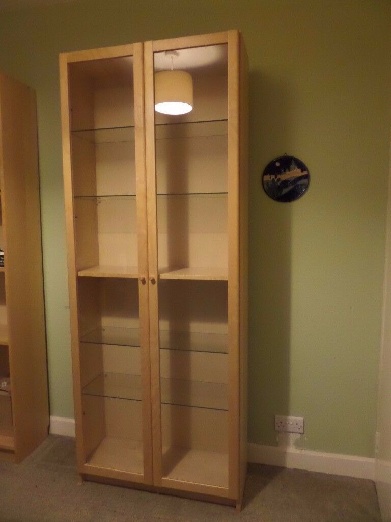 2 Ikea Billy bookcases in birch veneer with Oxberg glass doors, glass shelves, and lights