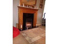 Wooden fire surouund with black marble harth, black marble back panel and electric fire.