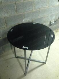 Cross metal frame with black tempered glass round top table.