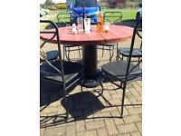 Upcyled cable drum table with black marble bottom and 6 wrought iron chairs with wooden seats