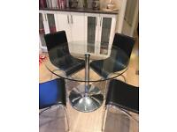 John Lewis glass round table with chrome base and four black leather chairs in very good condition