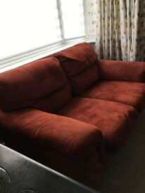 1 two and 1 three seater reddish sofas, matching pouffe and 2 matching pictures
