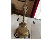 Antique brass bell with ornate handle showing face & 'crown'