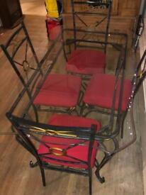 Wrought iron & glass dining table with four chairs - very heavy