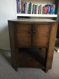 Wooden side table with small felt-lined cupboard