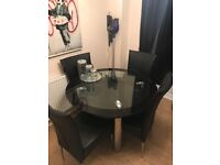 Harveys Round Glass Dinning Table And Four Faux Leather Chairs