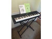 Electric Casio keyboard with stand and song book