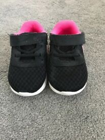 Black Nike trainers with pink trim and pink Nike logo. Size - UK 4.5