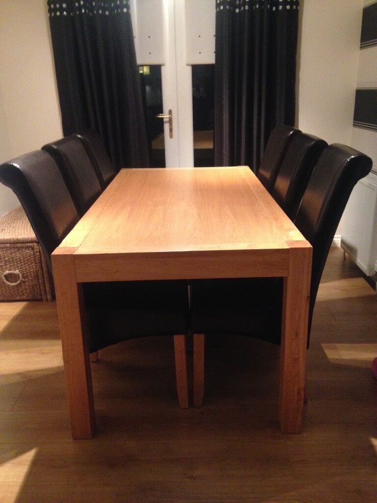 Solid Oak dining table and 6 brown faux leather sleigh chairs