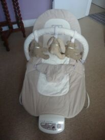 Mamas and Papas baby bouncer in beige with battery operated sound department at base..