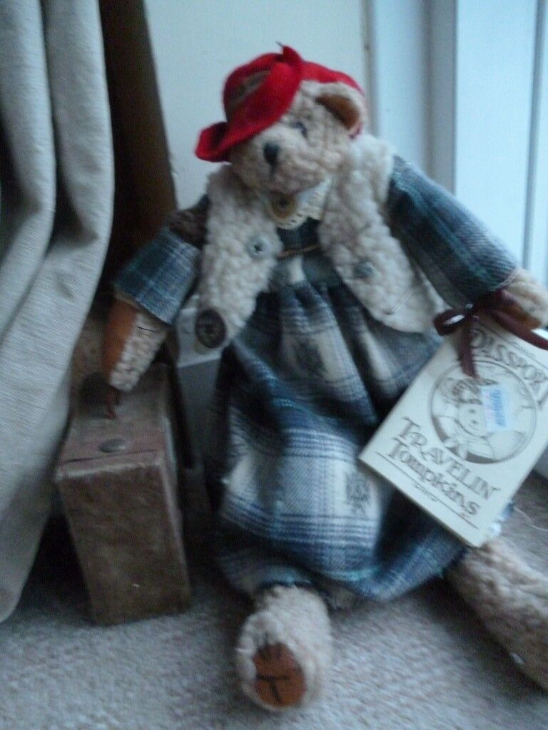 'Travellng Tompkins' bear on stand with suitcase and passport