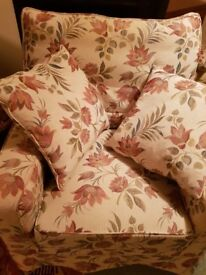 Large armchair with floral loose covers, cushions and matching footstool